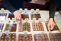 """24 October, 2008. New York, NY. Owner Namhee Girerd Kim, 53, picks an assortment of bon bons and fills a box at the boutique """"L'atelier du chocolat"""". The chocolates are made by her husband, Eric Girerd. The stand at the entrance of the shop displays an assortment of chocolate bon bons, including flavors such as herbs. salt, fruit, spices, and classic chocolates.<br /> <br /> ©2008 Gianni Cipriano for The New York Times<br /> cell. +1 646 465 2168 (USA)<br /> cell. +1 328 567 7923 (Italy)<br /> gianni@giannicipriano.com<br /> www.giannicipriano.com"""