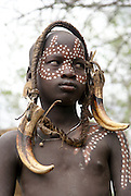 Africa, Ethiopia, Debub Omo Zone, Child of the Mursi tribe. A nomadic cattle herder ethnic group located in Southern Ethiopia, close to the Sudanese border. Woman with clay lip disc as body ornaments