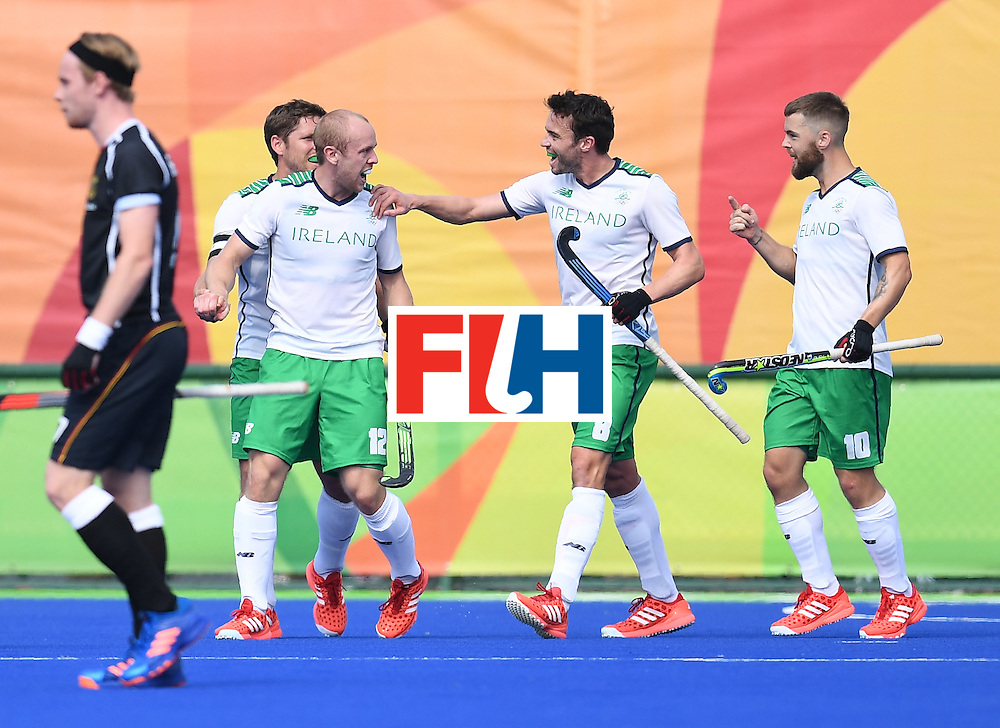 Ireland's Eugene Magee (2L) celebrates scoring a goal during the men's field hockey Germany vs Ireland match of the Rio 2016 Olympics Games at the Olympic Hockey Centre in Rio de Janeiro on August, 9 2016. / AFP / MANAN VATSYAYANA        (Photo credit should read MANAN VATSYAYANA/AFP/Getty Images)