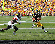 August 31 2013: Iowa Hawkeyes quarterback Jake Rudock (15) heads for the end zone on a 6 yard touchdown run as Northern Illinois Huskies safety Dominique Ware (24) closes in during the second quarter of the NCAA football game between the Northern Illinois Huskies and the Iowa Hawkeyes at Kinnick Stadium in Iowa City, Iowa on August 31, 2013. Northern Illinois defeated Iowa 30-27.