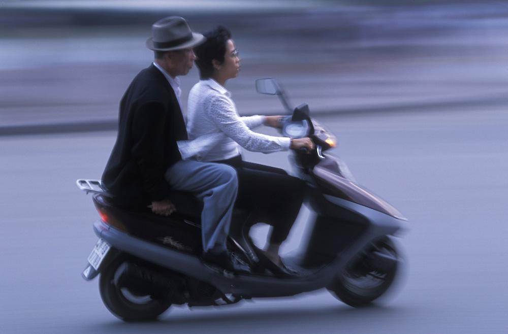 Asia, Vietnam, Hanoi, Blurred image of motorcycle traveling around traffic circle near West Lake (Ho Tay)