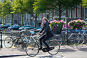 Young woman cycling across bridge in Amsterdam, Holland