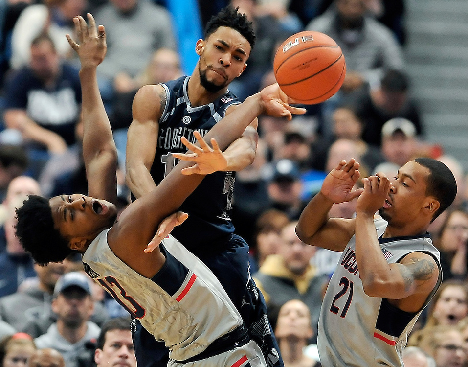 Connecticut's Steven Enoch, left, stops a drive to the basket by Georgetown's Isaac Copeland, center, as Connecticut's Omar Calhoun, right, defends, in the first half of an NCAA college basketball game, Saturday, Jan. 23, 2016, in Hartford, Conn. (AP Photo/Jessica Hill)