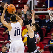 09 March 2018: San Diego State men's basketball takes on Nevada in the quarterfinal round of the Mountain West Conference Tournament. San Diego State Aztecs forward Max Montana (10) gets in the face of Nevada Wolf Pack forward Caleb Martin (10) as he attempts a three point shot in the first half. The Aztecs cruise past the Wolfpack 90-73 to move on to the Championship game tomorrow afternoon at 3pm.<br /> More game action at www.sdsuaztecphotos.com