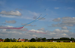 © Licensed to London News Pictures. 13/05/2015. Scampton, UK. The village of Scampton in Lincolnshire is surrounded by oil seed rape blossom as the RAF Red Arrows train overhead before the start of their summer display season. Photo credit : Anna Gowthorpe/LNP