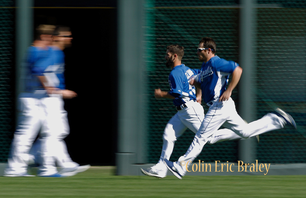Kansas City Royals relief pitchers Tim Collins, left and Greg Holland, right, run before a baseball game against the Texas Rangers at Kauffman Stadium in Kansas City, Mo., Saturday, Sept. 21, 2013. (AP Photo/Colin E. Braley)