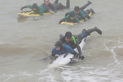 © Licensed to London News Pictures. 11/03/2017. Brighton, UK. Members of the Brighton surf life saving club take part in their weekly training session as a thick cloud of fog hangs over Brighton and Hove beach. Photo credit: Hugo Michiels/LNP