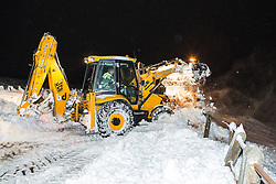 © Licensed to London News Pictures . 24/03/2013 . Burnley , UK . A JCB operator works to scoop and plough through a large snow drift to clear Halifax Road . The operator is working an 18 hour shift . Snowdrifts are making roads impassable around Burnley overnight (23rd/24th March) as high winds blow snow across roads . Plummeting temperatures and treacherous conditions are reported to have taken the life of a man named locally as Gary Windle . Lancashire Police reported finding a 27 year old man dead in deep snow yesterday (23rd March) afternoon . Photo credit : Joel Goodman/LNP