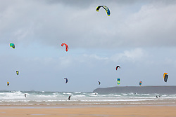 © Licensed to London News Pictures. 27/06/2020. Newquay, UK. Kitesurfers enjoy windy weather at Watergate Bay, Cornwall. The weather is variable with sunny outbreaks and rainy showers. Photo credit : Tom Nicholson/LNP