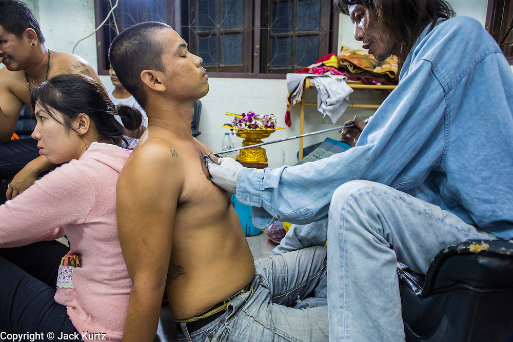 """22 MARCH 2013 - NAKHON CHAI SI, NAKHON PATHOM, THAILAND: Man leans against his girlfriend while getting a sacred Sak Yant tattoo at Wat Bang Phra. Wat Bang Phra is the best known """"Sak Yant"""" tattoo temple in Thailand. It's located in Nakhon Pathom province, about 40 miles from Bangkok. The tattoos are given with hollow stainless steel needles and are thought to possess magical powers of protection. The tattoos, which are given by Buddhist monks, are popular with soldiers, policeman and gangsters, people who generally live in harm's way. The tattoo must be activated to remain powerful and the annual Wai Khru Ceremony (tattoo festival) at the temple draws thousands of devotees who come to the temple to activate or renew the tattoos. People go into trance like states and then assume the personality of their tattoo, so people with tiger tattoos assume the personality of a tiger, people with monkey tattoos take on the personality of a monkey and so on. In recent years the tattoo festival has become popular with tourists who make the trip to Nakorn Pathom province to see a side of """"exotic"""" Thailand. The 2013 tattoo festival was on March 23.    PHOTO BY JACK KURTZ"""