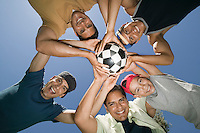 Boy (13-15) with brothers and father holding soccer ball together view from below.