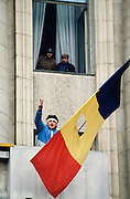 December 26, 1989. Bucharest, Rumania. The Rumanian flag with a hole instead of Communist insignia soon became the symbol of the revolution, here being waved from a balcony of the Central Committee. (Photo Heimo Aga)