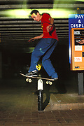 Skater, Robert Jaye, doing a rail-slide on a metal barrier in a car park, UK, 2000's
