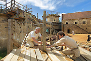 Builders and carpenters working on the wooden scaffolding in the courtyard, with the North Range or Logis Seigneurial and the Chapel Tower behind, at the Chateau de Guedelon, a castle built since 1997 using only medieval materials and processes, photographed in 2017, in Treigny, Yonne, Burgundy, France. The Guedelon project was begun in 1997 by Michel Guyot, owner of the nearby Chateau de Saint-Fargeau, with architect Jacques Moulin. It is an educational and scientific project with the aim of understanding medieval building techniques and the chateau should be completed in the 2020s. Picture by Manuel Cohen