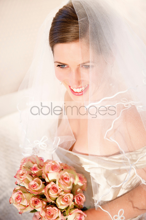 Close up of a smiling bride wearing a veil and holding a bouquet of roses