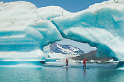 Two paddleboarders paddle under a large archway of ice at Bear Glacier in Kenai Fjords National Park near Seward, Alaska.