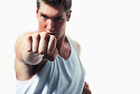 Caucasian Man throwing a punch.  Focus on his knuckles and fist.<br />