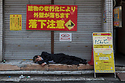 A salaryman sleeping in the streets of Kabukicho in Shinjuku, Tokyo, Japan. Friday July 10th 2015