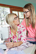 Mature mother looking at daughter while sewing cloth