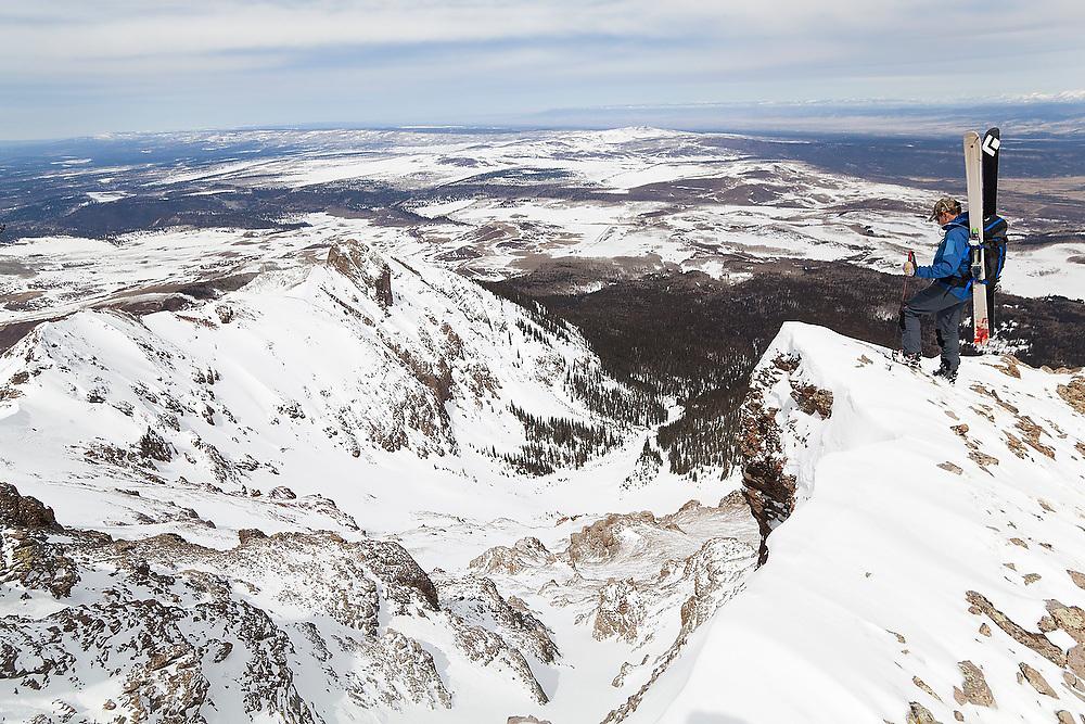 Backcountry skier Sterling Roop looks down from the summit ridge of Hayden Peak, San Juan Mountains, Colorado.