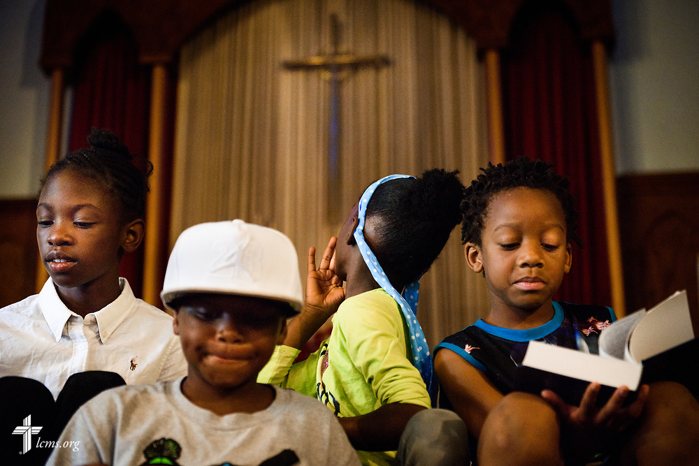 A young camper turns to examine the altar cross as fellow campers listen to a Bible story during vacation Bible camp at East Bethlehem Lutheran Church, Detroit, Mich., on Wednesday, June 21, 2017, in Detroit. LCMS Communications/Erik M. Lunsford
