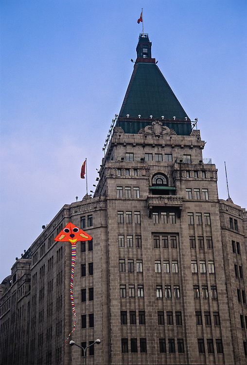 A kite soars above The Bund with the historic Peace Hotel in the background