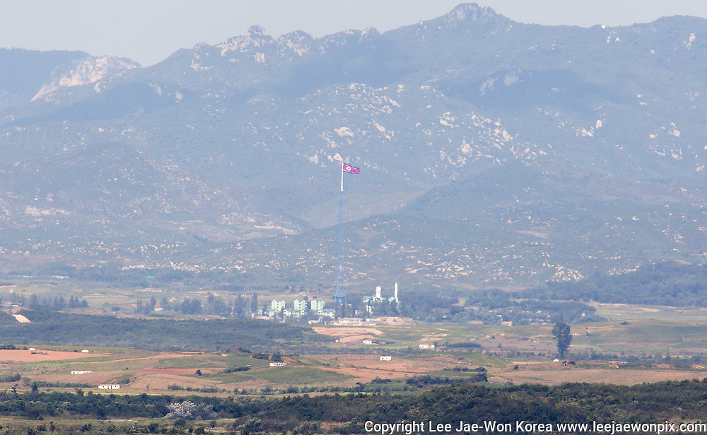 A North Korean flag on top of a tower in Gijungdong near the truce village of Panmunjom in the demilitarised zone (DMZ) separating two Koreas, is seen in this picture taken from a South Korean observatory, just about 2 km (1.2 miles) south of North Korean territory, in Paju, 35 km (22 miles) northwest of Seoul, South Korea, Sep 29, 2017. Photo by Lee Jae-Won (KOREA) www.leejaewonpix.com