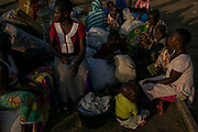 SEBAGORO, UGANDA - MARCH 23: Congolese refugees wait for transport to Kyangwali refugee settlement camp after landing in Sebagoro, Uganda on March 23, 2018. Violence in Ituri Province in northeastern Democratic Republic of Congo has displaced more than 100,000 people including approximately 40,000 refugees who have fled to Uganda. (Photo by Andrew Renneisen for The Washington Post)
