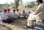 Young boys sit on open grass whilst a teacher checks the register in the grounds of their destroyed Nazarabad Government Boys School in SWAT....Some pupils have returned to the makeshift open-air class rooms whilst others still fear the return of the Taliban and choose to stay away from lessons. .