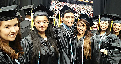 These East Early College High School students (black gown with blue cord) were some of the more than 100 seniors from that campus to receive their associate's degrees from Houston Community College SE two weeks before their high school diplomas.