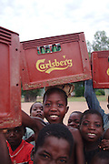 Africa. Malawi. Usisya Village..Children carrying crates of Carlsberg beer on their heads..CD0010
