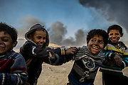 Children play in the smoke and soot of the oil fires unaware of the damage that released carcinogens will do to their developing bodies for many years to come. Qayyara, Iraq. Nov. 23, 2016. (Photo by Gabriel Romero ©2016)