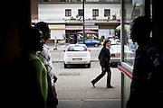 Una donna di passaggio osserva i migranti di una delle ex palazzine olimpiche.