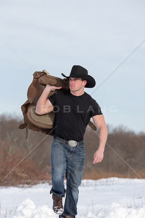 cowboy holding a saddle walking through the snow on a ranch