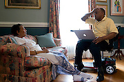 Johnny Lewis speaks with his wife, Shirley, as they look at photographs at their home in Fort Worth, Texas on April 21, 2014. Johnny is the caretaker for Shirley who has been diagnosed with ALS. (Cooper Neill / for AARP)