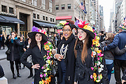 New York, NY, USA-27 March 2016. Three women wearing hats by Patricia Daher pose on New York's Fifth Avenue at the annual Easter Bonnet Parade and Festival.