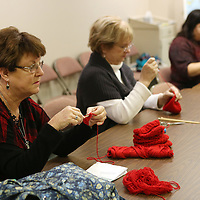 Lauren Wood   Buy at photos.djournal.com<br /> Cindy Kirk, from left, Vivian Fleming and Becki Depew work on making newborn-baby-sized red caps Tuesday evening at First Presbyterian Church.