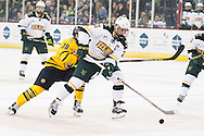 Vermont's Mario Puskarich (21) skates with the puck past Quinnipiac's Craig Martin (20) during the men's hockey game between the Vermont Catamounts and the Quinnipiac Bobcats in the championship game of the Friendship Four hockey tournament at the SSE Arena on Saturday evening November 26, 2016 in Belfast, Ireland. (BRIAN JENKINS/for the FREE PRESS)