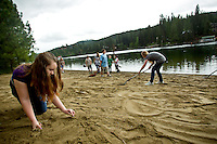 "JEROME A. POLLOS/Press..Cassidy Huckaby, 11, clears weeds out of the freshly spread sand on the beach Tuesday at Kiwanis Park in Post Falls. Huckaby, a fifth-grade student from Ponderosa Elementary, was part of a team of more than 100 students from the school who took part in the ""Take Pride in America"" program that encourages and recognizes efforts that promote taking pride by taking care of public lands."