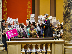 May 4, 2017 - St. Paul, Minnesota, United States - A Protestant minister reads bible passages supporting workers and women's rights in front of the Minnesota State Senate. About 200 people participated in a ''ISAIAH's 100 Days of Prophetic Resistance'' rally at the Minnesota State Capitol in St. Paul. They represented churches from across the Twin Cities and were demonstrating in favor of paid sick leave, child care, and a higher minimum wage. The Twin Cities are more liberal than rural Minnesota and many Twin Cities municipalities have passed ordinances with paid sick leave, child care and higher minimum wages. Republican legislators from rural Minnesota have tried to pass laws in the legislature rolling back those ordinances. (Credit Image: © Jack Kurtz via ZUMA Wire)