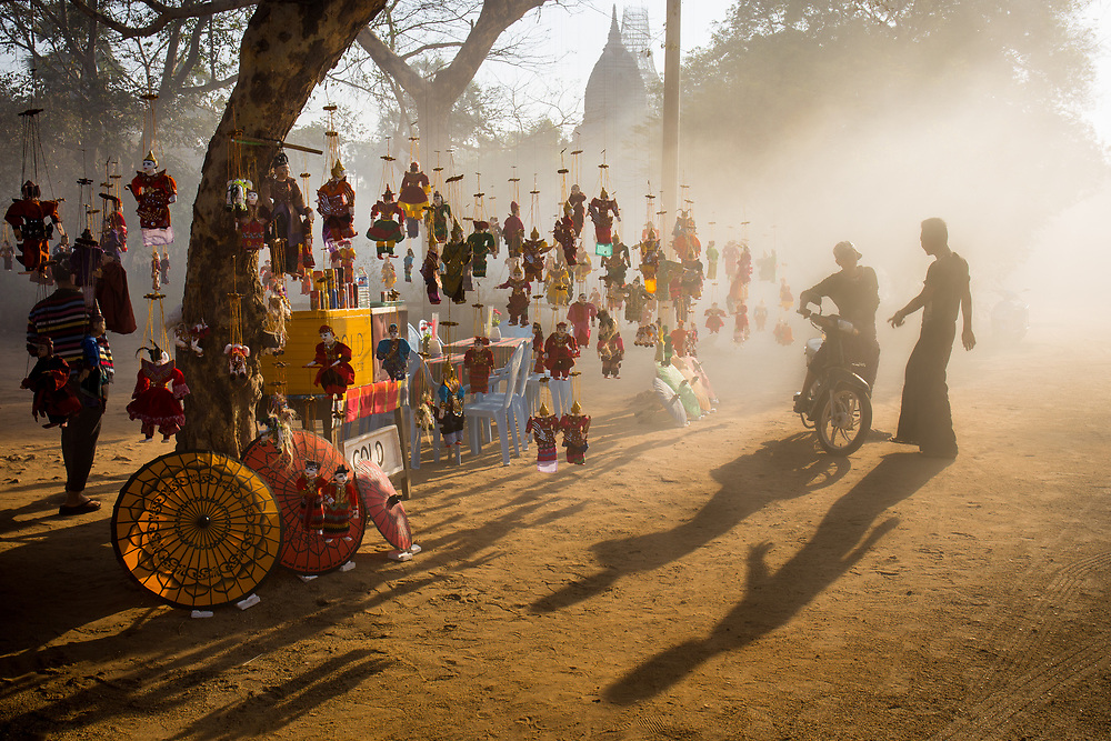 The mist of the morning envelop a Burmese Puppet stall illuminated by the first sun rays.<br /> Photo by Lorenz Berna