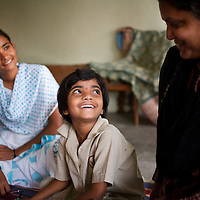 "Vasanti (left) with her youngest daughter Vrinda and her teacher at the school she attends in Sangli. ..Like many of the women who work for and with UNDP partners the Save Foundation, Vasanti Shinde, age 26, only found out that she was HIV positive after her husband became seriously ill with an AIDS-related illness five years ago. Vasanti's husband subsequently died. Vasanti now lives with her two younger daughters Shrudha, age 10, and Vrinda, 8, in the one-room home of her brother in Sangli city. Vasanti's elder daughter, eleven year old Shubhada is being brought up by her paternal grandmother and sees her mother during holidays. Vasanti knows that Shubhada is HIV negative and Shruda is positive but anxiety over the result means that she refuses to have Vrinda tested for HIV. For a monthly income of Rs.3500, Vasanti works as a field officer and counselor for the Save Foundation. She works in the positive-people's pharmacy for no pay. Her work with the Save Foundation entitles her access to a credit union which provides low interest loans covering medical expenses. Though first-line drugs and homeopathic medicine keep Vasanti healthy, she is prone to infection and recently suffered a bout of influenza. Vasanti is completely open about her HIV status and most of her neighbours know that she is HIV positive. Vasanti says that ""I used to feel like I was going to die. Now, because of the Save Foundation, I feel like I'm going to live."" ..Photo: Tom Pietrasik.Sangli, Maharashtra. India.August 27th 2008..THIS PHOTOGRAPH IS THE COPYRIGHT OF TOM PIETRASIK. THE PHOTOGRAPH MAY NOT BE REPRODUCED IN ANY FORM OTHER THAN THAT FOR WHICH PERMISSION WAS GRANTED. THE PHOTOGRAPH MAY NOT BE STORED OR MANIPULATED WITHOUT PRIOR PERMISSION FROM TOM PIETRASIK...Tom Pietrasik.PHOTOGRAPHER.NEW DELHI.India tel: +91 9810614419.UK tel: +44 7710507916.Email: tom@tompietrasik.com.Website: tompietrasik.com"