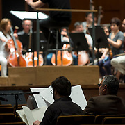 June 3, 2014 - New York, NY : As part of the New York Philharmonic Biennial, the orchestra solicited pieces from little-known composers and will choose three to play. Pictured here, Philharmonic Music Director Alan Gilbert, on podium in distance, leads the New York Philharmonic as it performs a composition by composer Max Grafe, who is visible at foreground left working with mentor composer Robert Beaser, right, on Tuesday. CREDIT: Karsten Moran for The New York Times