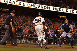 September 12, 2011; San Francisco, CA, USA;  San Francisco Giants center fielder Andres Torres (56) scores a run past San Diego Padres catcher Nick Hundley (right) in front of MLB umpire Brian Gorman (left) during the seventh inning at AT&T Park.
