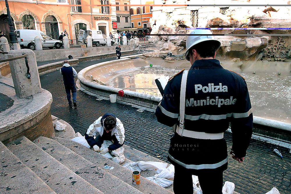 Rome 18 November 2006.The collected of coins thrown by tourists into the Trevi Fountain for express a wish is made by the staff of Caritas of Rome and used to finance the Emporio Caritas..Operation that takes place once a week.The fountain was built by the architect Salvi (1735) in the time of Pope Clement XII, and decorated by several artists of Bernini's school.The municipal police check the collected of coins..La  raccolta delle monete gettate dai turisti dentro Fontana di Trevi per esprimere un desiderio viene effettuata dal personale della Caritas Diocesana di Roma  e servono a finanziare l?Emporio Caritas..Operazione che viene effettuata una volta a settimana.