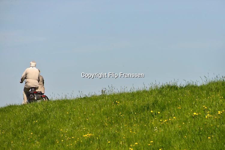 Nederland, Millingen ad Rijn, 21-4-2016Ouderen maken een fietstochtje over de dijk langs de Waal, Rijn . Het is een mooie dag met zon en een blauwe lucht. Het fietspad loopt over de dijk vanuit Duitsland en wordt veel gebruikt door Duitse toeristen .FOTO: FLIP FRANSSEN/ HOLLANDSE HOOGTE