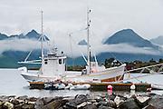 A ship docks beneath mountains on Moskenesøya (the Moskenes Island) at Selfjorden, in the Lofoten archipelago, Krystad village, Nordland county, Norway