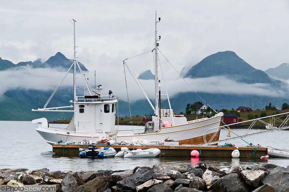 A ship docks beneath mountains on Moskenesøya (the Moskenes Island) at Selfjorden, in the Lofoten archipelago, Krystad village, Nordland county, Norway