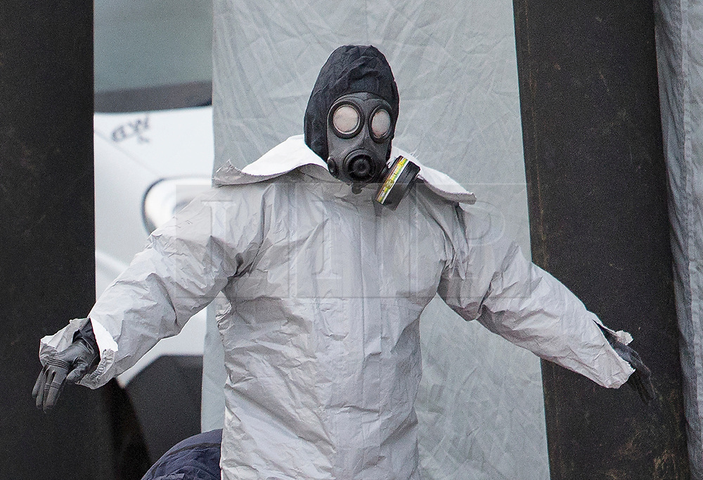 © Licensed to London News Pictures. 15/03/2018. Alderholt, UK. Police in gas masks start to remove their protective overalls at Ashley Wood Recovery in Salisbury where the car belonging to former Russian spy Sergei Skripal was taken after he and his daughter Yulia were poisoned with nerve agent. The couple where found unconscious on bench in Salisbury shopping centre. A policeman who went to their aid is currently recovering in hospital. Photo credit: Peter Macdiarmid/LNP