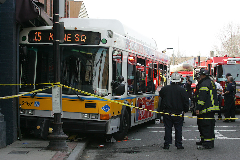 Boston, MA 04/11/2011.Boston Police officers inspect a Route 15 bus that crashed into a building at the intersection of Dudley St. and Hampden St. after passengers assaulted the bus driver on Monday afternoon. .Alex Jones / www.alexjonesphoto.com